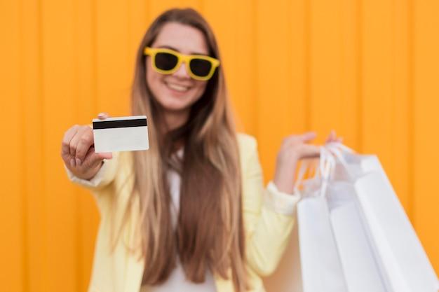 쇼핑 카드를 들고 노란색 옷을 입고 여자 무료 사진