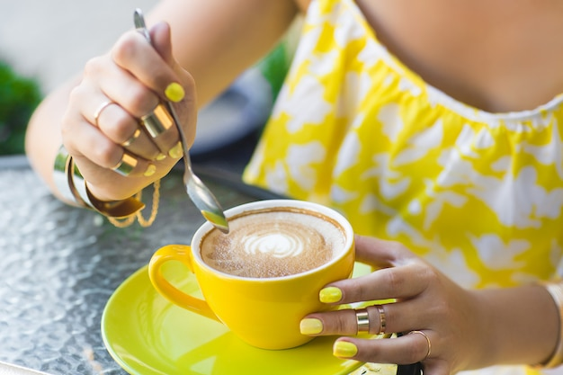 Woman wearing yellow dress drinking coffee. young unrecognizable girl with yellow manicure outdoors. close up still of fingers with bright nail polish Premium Photo