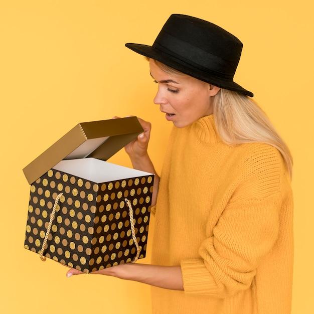 Женщина в желтой рубашке смотрит в подарочную коробку Бесплатные Фотографии