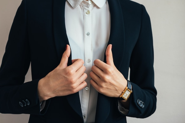 Woman wears a business suit jacket. in her hand wristwatch Premium Photo
