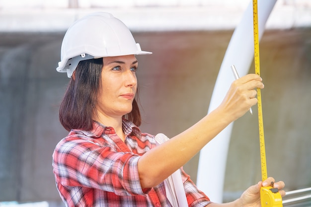 Woman wears white safety hat is working at construction site Premium Photo