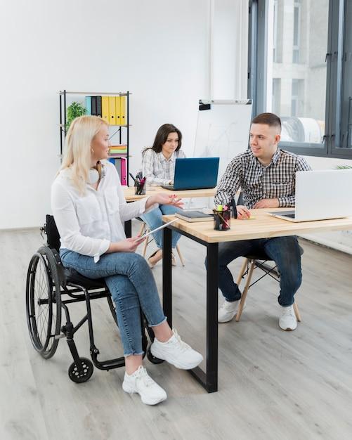 Donna in sedia a rotelle che discute con il collega allo scrittorio Foto Gratuite