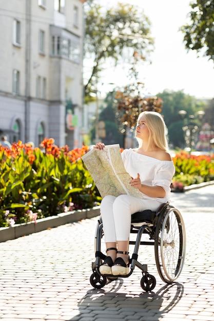 Donna in sedia a rotelle guardando la mappa all'esterno Foto Gratuite