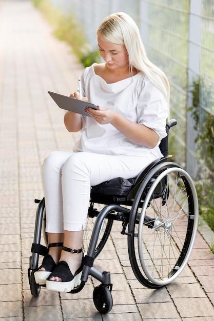 Donna in sedia a rotelle all'aperto con tablet Foto Gratuite