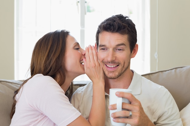Woman whispering secret into a happy mans ear in living room Premium Photo