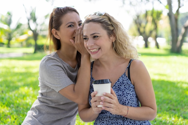 Woman whispering secret to smiling girlfriend in park Free Photo