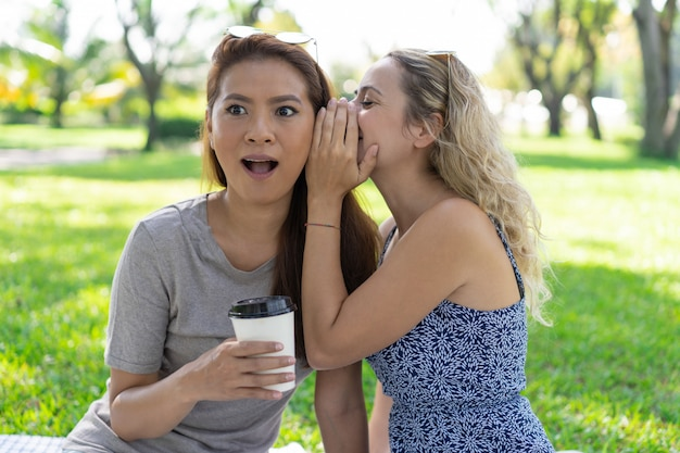 Woman whispering secret to surprised female friend in park Free Photo