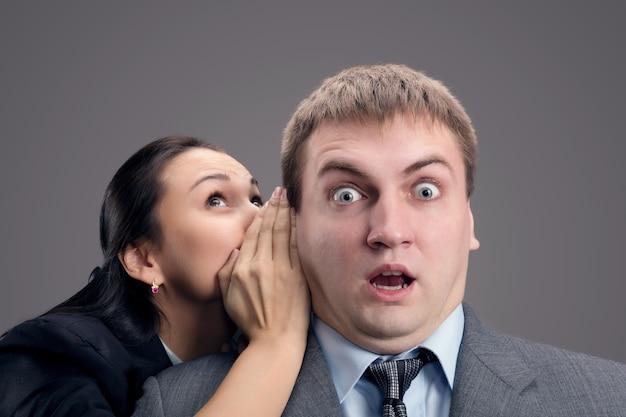 Женщина шепчет мужчине Premium Фотографии