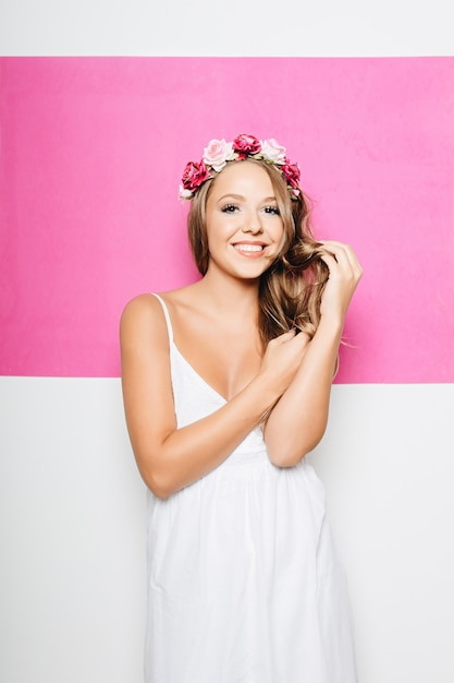 Woman in white cotton dress with flowers in hair smiling Free Photo