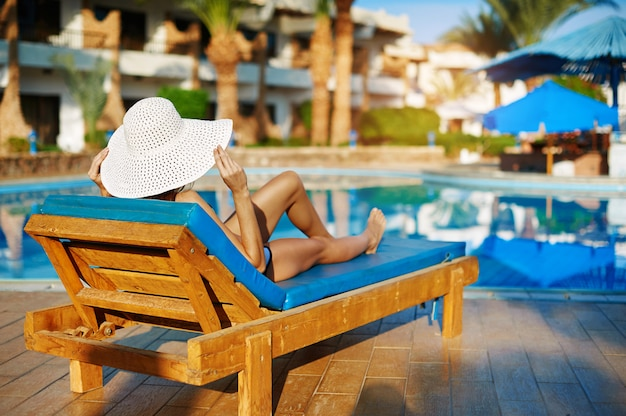 Woman in white hat lying on a lounger near the swimming pool at the hotel Premium Photo