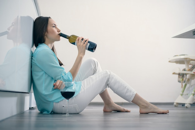 A woman in white jeans and a turquoise shirt sits on the floor in the interior of a white kitchen and drinks red wine from a bottle, divorce, alcohol, parting, grief, dependence, fatigue Premium Photo