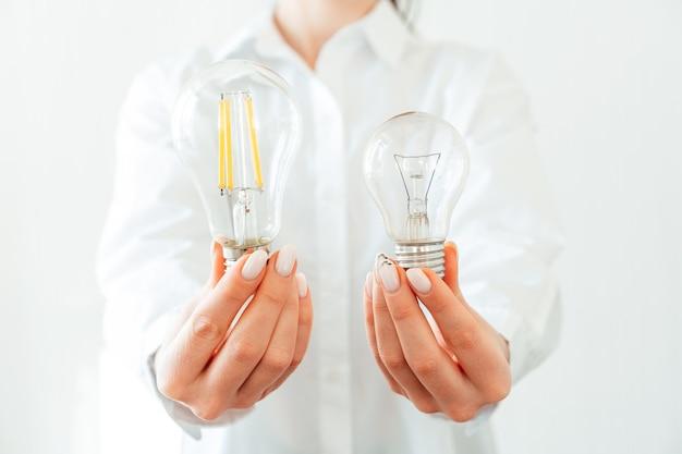 Woman in white shirt holding light bulb in hand Premium Photo