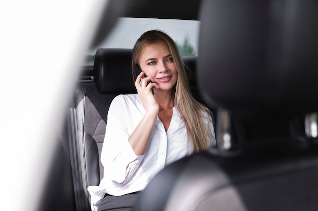 Woman in white shirt sitting in car and talking at the phone Free Photo