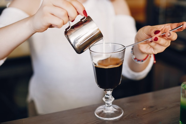 Woman in a white sweater pouring milk into coffee dessert Free Photo