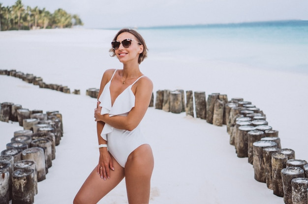 Woman in white swimming suit by the ocean Free Photo
