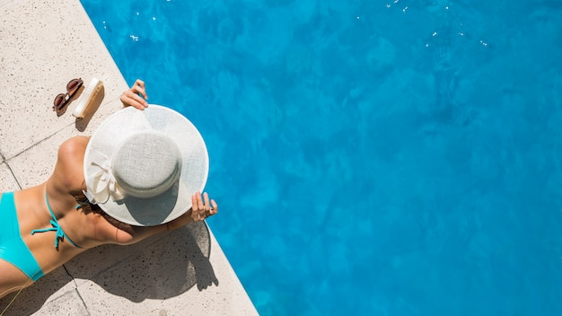 Woman in wide-brimmed hat lying on pool border Free Photo
