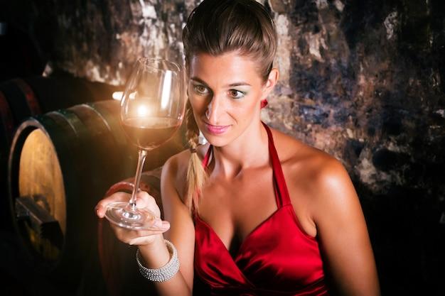 Woman in wine cellar with barrels tasting Premium Photo