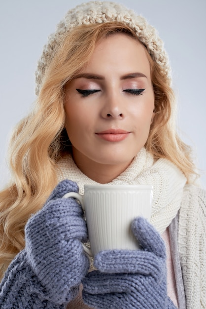 Woman in winter clothes drinking delicious coffee to get warm Free Photo