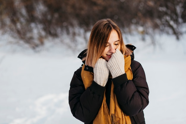 Woman in winter clothes warming hands Free Photo