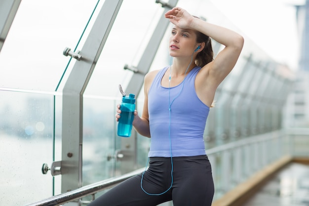 Woman wiping sweat from forehead while holding a water bottle Free Photo