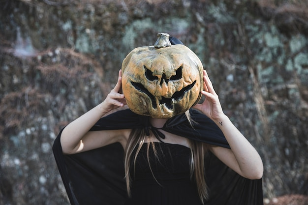 Woman in witch costume closing face by frightful pumpkin Free Photo
