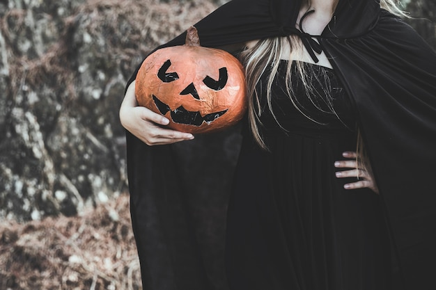 Woman in witch costume holding pumpkin Free Photo