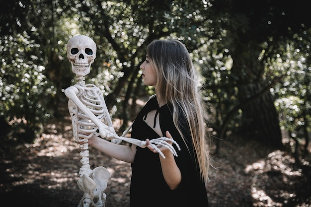 Woman in witch costume holding skeleton Free Photo