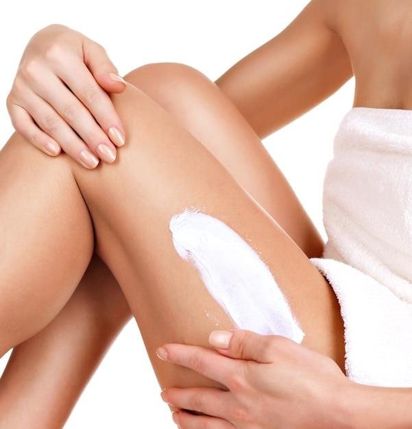 흰색에 그녀의 다리에 크림을 사용하여 아름다운 몸매를 가진 여자 무료 사진