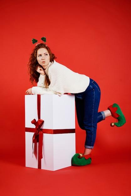 コピースペースを見ている大きなクリスマスプレゼントを持つ女性 無料写真