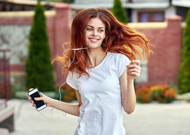 電話とヘッドフォンを持つ女性 Premium写真