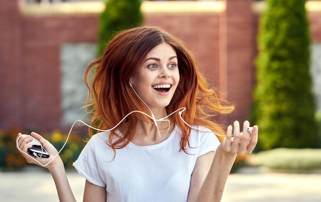 ヘッドフォンで携帯電話を持つ女性 Premium写真