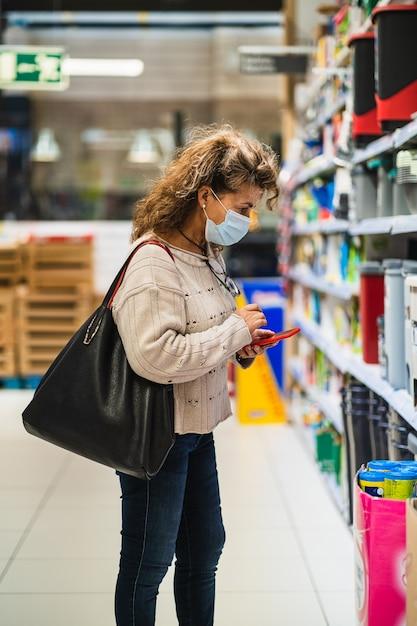 スーパーマーケットでマスクを着用しながら購入する商品を選ぶスマートフォンを持つ女性 Premium写真