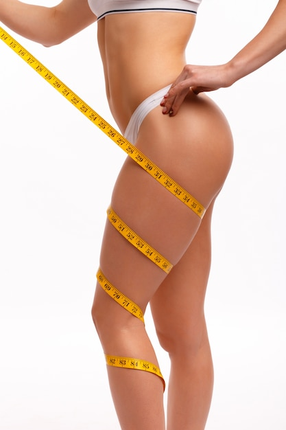 Woman with a tape measure wrapped around her leg Free Photo