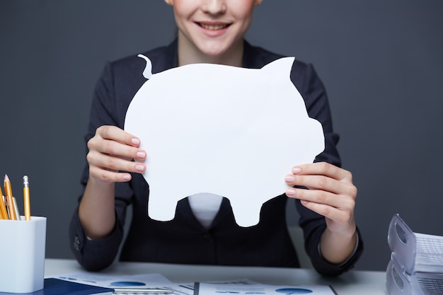 Woman with a white piggy bank Free Photo