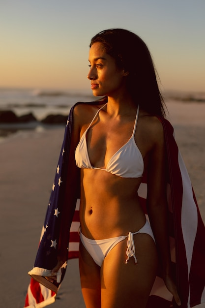 Woman with an american flag standing on the beach Free Photo