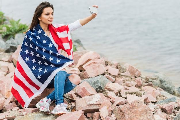 Женщина с американским флагом, берущим себя рядом с водой Бесплатные Фотографии