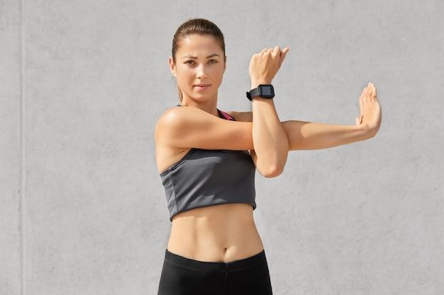 魅力的な表情の女性、運動をする、手を伸ばす、カジュアルなトップスを着ている、健康を管理するためのスマートウォッチ 無料写真