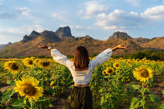 Woman with arms raised in sunflower field at kao jeen lae in lopburi, thailand Premium Photo