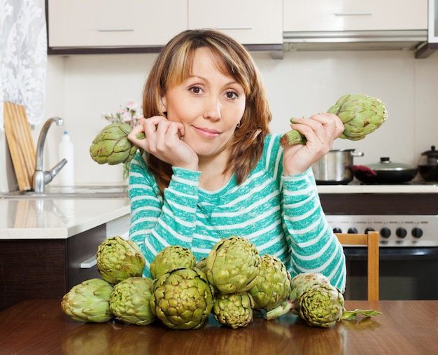 Woman with artichokes Free Photo