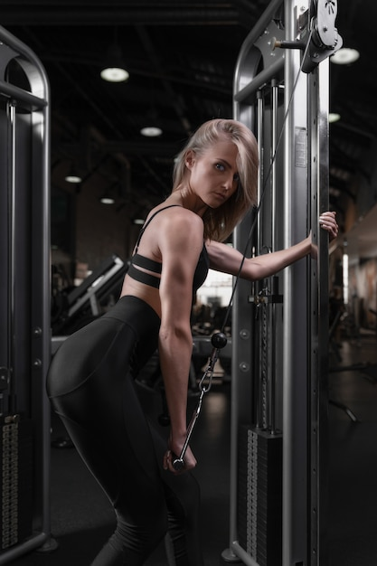 A woman with an athletic physique trains in a fitness club works out triceps by unbending one arm in a crossover holding on to a rope Premium Photo