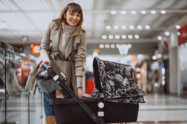 Woman with baby carriage in shopping mall Free Photo