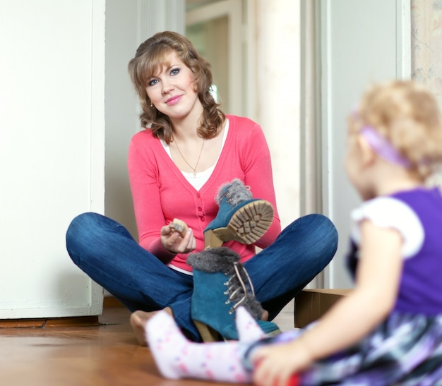 Woman with baby cleans footwear Free Photo