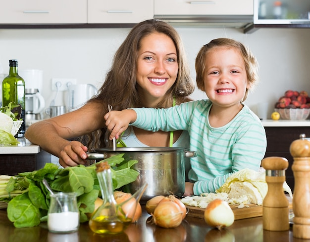 Woman with baby cooking at kitchen Free Photo