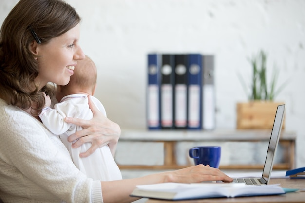 Woman with a baby looking at his laptop Premium Photo