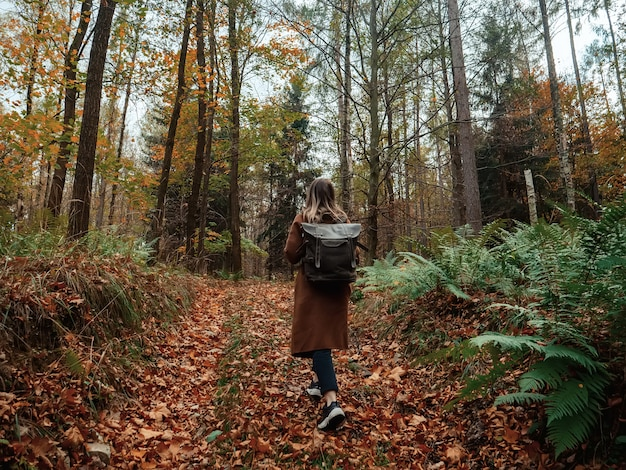 Woman with a backpack in the autumn forest Premium Photo