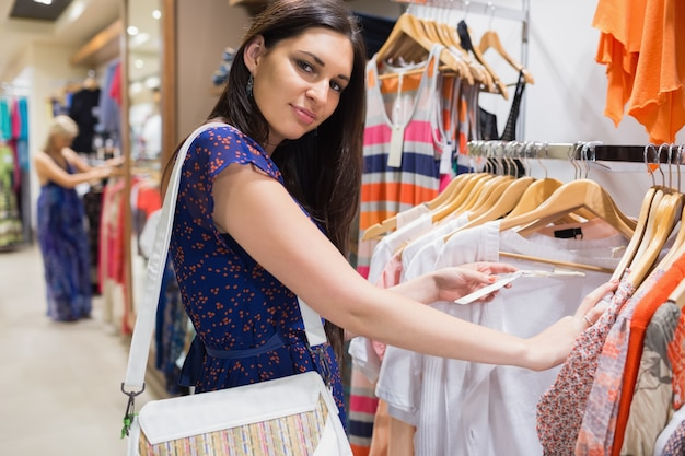 Woman with bag looking through clothes and smiling Premium Photo