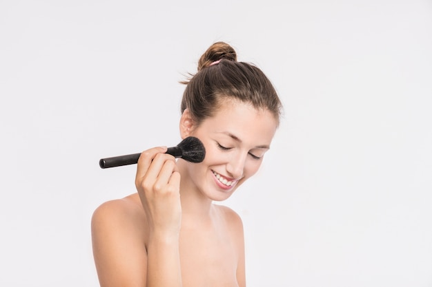 Woman with bare shoulders using powder brush Free Photo