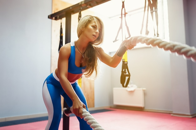 Woman with battle ropes exercise in the fitness gym. young female wearing sportswear. Premium Photo