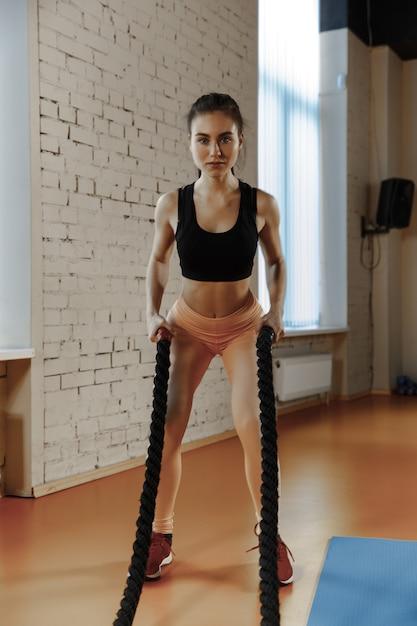 バトルロープを持つ女性は、フィットネスジムで運動します。アスリート、スポーツ、ロープ、トレーニング、トレーニング、エクササイズ、健康的なライフスタイルの概念 無料写真