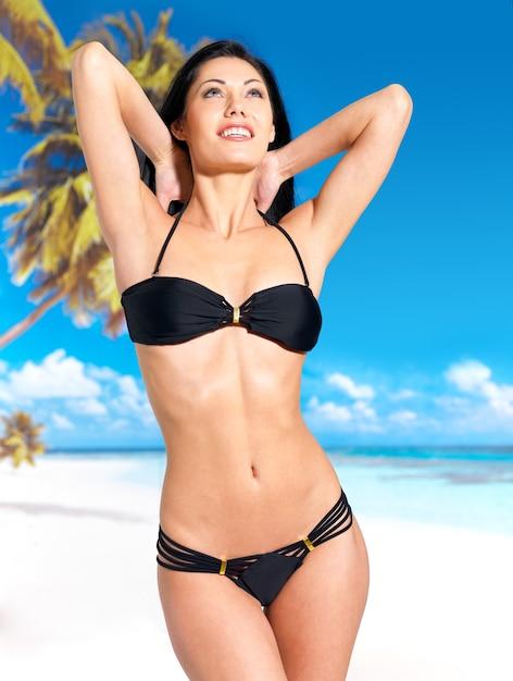 검은 비키니 입은 아름다운 몸매를 가진 여인이 해변에서 일광욕 무료 사진
